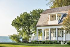 """""""The home's design was inspired by the late-19th-century Shingle-style architecture along the coast of Maine, with its abundance of porches to capture the all-too-short summers that Chicagoans are all too familiar with,"""" Liederbach says. Here, however, practicality dictated a painted finish rather than natural weathered wood shingles. Wood Staircase, Grand Staircase, Shingle Style Architecture, Chicago Buildings, Wood Shingles, Lakefront Homes, Gambrel, Wood Panel Walls"""