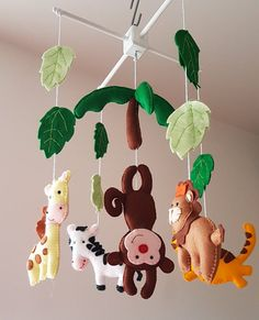 Baby cot/ crib mobile with lovely jungle animals. It will take you and your baby on a great adventure and cute monkey will leave smile on your babys face. Each nursery mobile character is hand cut and hand sewn by me with loads of love and eye for a details. I made the wooden mobile as well. This baby mobile will be a perfect gift for a newborn and fantastic nursery decoration. Mobile includes: 6 felt characters, each is approx 15 cm high plus some jungle leafs so you will feel like yo...