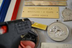 what to do with all those trophies- attaching plaques and medals with hot glue