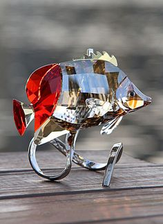 """Swarovski Butterflyfish, Light Siam   $475.00 4 3/4""""   Item# 1040347    Inspired by the diverse marine life of the Red Sea, the exquisite Butterflyfish has been captured in exclusive Swarovski crystal. This beautiful species can be found in a reef environment.  Its body glows in faceted Golden Shine, Satin and Copper crystal, with a Light Siam red crystal back. Elegantly placed on a silver-tone metal display with an embossed coral motif, it makes an eye-catching centerpiece."""