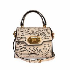This stunning Dolce & Gabbana bag is unique and sophisticated, crafted of luxuriously calfskin leather printed with warm messages of welcome.  ITEM CONDITION: Pre-owned – Excellent condition.  SUPPLIED WITH: This item is supplied with a Luxity dust bag.  SIZE: (Length) 24 cm x (Height) 19.5 cm x (Width) 12 cm x (Drop) Adjustable.  INTERIOR: Very good condition – With normal signs of wear and has a few marks.  BAG EXTERIOR : Excellent condition – With minimal signs of wear. Graffiti Prints, Dust Bag, Minimal, Satchel, Ivory, Exterior, Drop, Messages, Warm