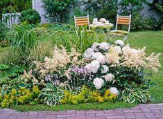 I takto může vypadat ostrůvek či záhon osazený trvalkami; zde mimo jiné hortenzie, bohyšky a traviny. Ilustrační foto
