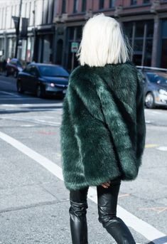bleach blonde bob, green fur coat and leather pants