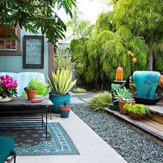 love the colors, wood. plants in pots and use of outdoor rug to define seating area by amalia