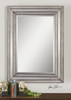 "This mirror features a frame made of antiqued mirror inlays with burnished silver details. Center mirror features a generous 1 1/4"" bevel. May be hung horizontal or vertical."