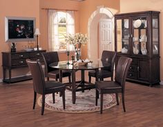 Light Salmon Color for Dining Room Painting Ideas with Simple Wood Dining Table on the Simple Rounded Shaped Carpet that have Glass Round Countertop Style and Sweet Brown Leather Chairs Cover Decorating also Traditional Brown Wood Cabinet Furniture on the Solid Wood Flooring
