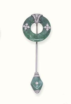 AN ART DECO JADEITE AND DIAMOND JABOT PIN   The top designed as a jadeite disc, enhanced by diamond-set florets and tapered detailed, to the navette-shaped jadeite terminal, with a central collet diamond and diamond-set trim, circa 1920