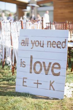 All you need is love DIY negative space sign. Just cut the letters out of contact paper, stick them on the boards, paint over them, and remove the contact paper letters for a beautiful and inexpensive custom sign!