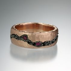 Todd Pownell's Rose Gold Fissure Cut Band is a lovely twist on traditional wedding jewelry. Inverted black diamonds and five rubies set into the darkened center of this 14k rose gold hammered band make those diamonds stand out even more. We think this ring is fabulous for your left or right hand. May we suggest adding this to a ring party?<br><br>Ring is 7mm wide and a size 7.5. Diamonds equal 0.70cttw.<br><br><br><br>