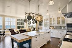 I love the hanging pot rack, it adds so much to the space! Although I don't think I would hang my real pots on it, they would get so dusty, but some old fashioned thrift store ones would look great. And I really like the white windowed cabinets, it's such a clean, bright look.