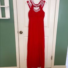 Red prom dress Red full length dress has slit on the left side goes to about thigh hight. Dress is 2 layers of fabrics silky material covered in sheer. Rainbow sequin and gems around the neckline. Zips up the back and buttons around the collar. Dresses