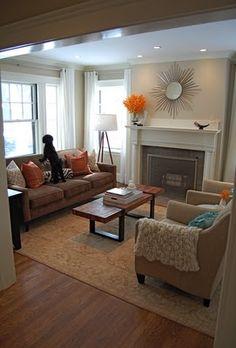 Benj Moore Manchester Tan Walls; love the sunburst mirror, orange accents ... and especially the 4-legged sofa accessory!