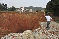A local resident throws a stone into a sinkhole near Qingquan primary school in Dachegnqiao town, Hunan province, on June 15, 2010. No causalities had been reported and the reason for the appearance of the hole remains unclear.