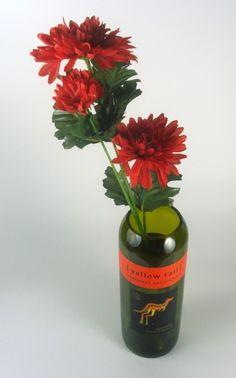 Recycled wine bottles as flower vases. Like!