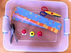 Strips of colored paper, hole puncher, scissors, and small shape hole punches: let children cut and punch holes on the strips of paper.