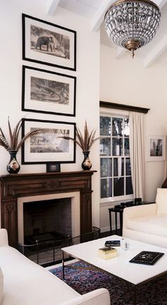Stacked antique etchings over the mantelpiece accentuates living room's cathedral ceilings.