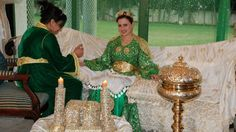 Bride getting the henna design put on her hands. She is sitting on a couch covered with a hand-embroidered silk cover; next to her is a brass incense burner. She is wearing a gold crown, fibulae, and a gold belt (very heavy!) Negafa Dar Bennani www.ziana.ma