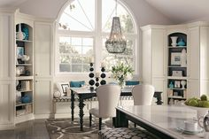 Built-in corner #cabinets with open shelves and a window seat create a distinctive dining area.