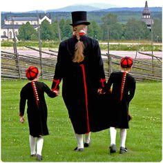 Skräddaren med söner. Mansdräkter från Delsbo socken. Delsbo kyrka i bakgrunden.