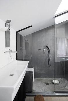 """Très jolie douche """"à l'italienne"""" en béton ciré. La paroi de douche, soulignée de noir, et qui suit le plafond des combles, est très chic."""