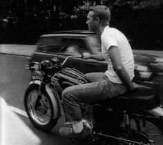 Steve McQueen one handed motorcycle in a white t-shirt and pair of jeans.