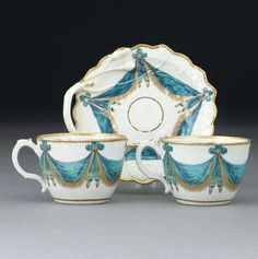 A Worcester 'Blind Earl' pattern sweetmeat dish and two teacups from the Lord Stormont service  CIRCA 1772  Each painted and gilt with turquoise drapery swags suspended from gilt dentil rims  The dish 6¼ in. (15.9 cm.) wide (3)