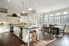 Large open concept kitchen with huge white island dividing the kitchen and the dining area. White cabinets and ceiling contrast with the dark wood floor throughout