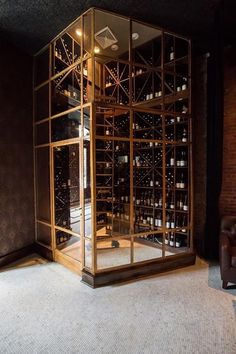 Glass and brass wine room boasts built in wine racks lined with a ladder. Wine cellar metal detail enclosure shower