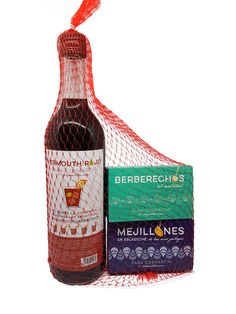 Elegante Pack de Aperitivos Premium. Las mejores conservas y vermut de Para Compartir by Tuaperitivo.com. Presentado en red de pescador color rojo, perfecto para disfrutar de un regalo gourmet.