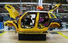 An employee installs a wiring loom into a Mini car at the BMW Mini car production plant in Oxford.