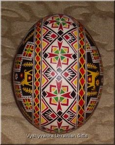 This pysanka has images of horses carrying the sun as well as numerous sun symbols.  The tripod (as part of the dominant sun symbol here) represent man, woman and child or birth, life, and death.
