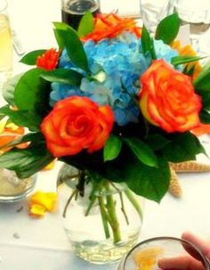 centerpiece, low, blue hydrangea, orange roses, foliage, breathtakingbridalbouquets.com