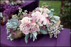 """Birch logs logs on either side of the """"MR"""" and """"MRS"""" will be filled with gray purple succulents, lavender spray roses, white Queen Anne's lace, pink astilbe, fresh lavender, gray dusty miller, green sage, and lavender stock flowers.  Mercury glass votives will be scattered around."""