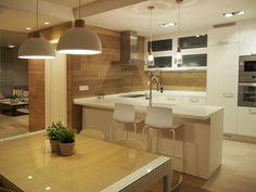 Cocina con office. Encimera realizada en solid surface donde se ubica barra para desayunos. Revestimiento de paredes en porcelánico imitación madera. Proyecto de diseño de interiores realizado y ejecutado por AZ diseño.