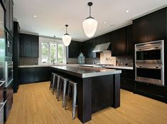 Dark cabinets, grey countertops and light wood floors.like the floor color with dark cabinets. Would go with lighter countertop though. Grey Countertops, Dark Kitchen Cabinets, Luxury Kitchens, Kitchen Remodel, Modern Kitchen, Contemporary Kitchen, Home Kitchens, Kitchen Renovation, Luxury Kitchen Design