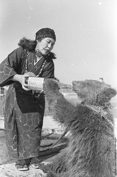 A captive bear drinking from a large sake bottle held by an Ainu tribeswoman, ca. 1955 by Evans/Three Lions