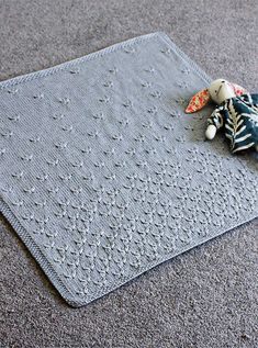 Knitting pattern for Dandelion Baby Blanket - This baby blanket uses the dandelion stitch to create the vision of dandelion fluff full of wishes blowing on the breeze. Designed by Leisl Shanley for Jorth Knits