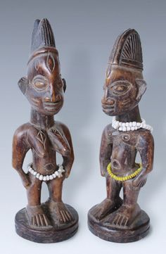 A fine  couple of ibeji -Twinfigures, Yoruba peoples, Nigeria  Finely rendered male and female figurines representing a matched pairs of twins. Attractive shown scarification marks on the face and breasts. Figures of this type are used in Ibedji cult and make it represents Ibedjis deceased twins (or ibeji) can sometimes also simply be used as a toy..  Material: made from medium weight wood carved from one piece, remnants of dark paint. Glass beads.