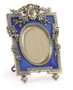 A FABERGÉ SILVER AND TRANSLUCENT ENAMEL PHOTOGRAPH FRAME, MOSCOW, CIRCA 1895 shaped rectangular, enamelled translucent blue over a sunburst guilloché ground, applied with foliate swags and ribbons, beaded bezel surrounding oval aperture, with wood back and shaped silver strut, struck K. Fabergé with Imperial Warrant, 88 standard, scratched inventory number 5536  Diameter 4 3/8 in.; 11 cm