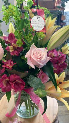 Bright roses, alstroemerias, lilies, Bupleurum, gerbera daisies and eucalyptus in a classic milk jug vase!