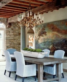 Everything about this room is gorgeous - painting, wood beams, stone, centerpiece, table, and chandelier!