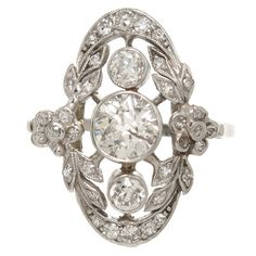 Edwardian Diamond Platinum Cocktail Ring. Circa 1910 Edwardian Platinum and Diamond Ring. Centrally set with a European cut Diamond of approximately .90 Carat that is fairly White and Clean and further set with numerous smaller European cut Diamonds totaling another .60 Carat. Measuring just over 3/4 inch in length and 5/8 inch wide.