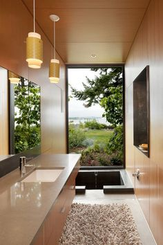 There is something so wonderful about not having to step over the side of a tub to get in and out. Using a sunken tub in this bathroom leaves an unobstructed view to the floor-to-ceiling window.