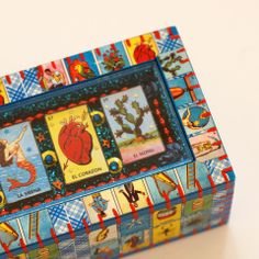 This one-of-a-kind, charming wooden box is expertly covered with lotería paper. The removable lid is similar to a shadow or nicho box. The inset 3-D display in the top of the box is decorated with several small lotería cards, and lots of shiny-ness, glitter and beads. So much detail and