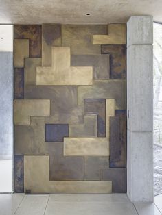 The material for the door is bronze. The different colored panels are achieved through the patina process.