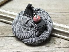 Handmade brooch from layers of satin fabric, nicely embellished with glass and ceramic beads. This rose brooch will make a prefect accessory for your wardrobe. It goes well with plain jackets, dresses. Colors: gre, black, white, rose ceramic bead Dimension: 3,34 (8,5cm) in diameter and is
