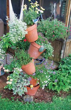 I really want top do this - can you buy terra cotta pots pretreated to not dry out so fast?  I could do a whole row in the yard.  Lovely images dancing through my head.  I agree with someone's comment about putting something cute at the top of the bar.  Maybe a birdhouse?