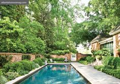 Tasked with designing a pool, the Planters team decided that the best place for it was off the Norman Askins-designed master suite addition. Also within the brick-fenced area are lush plantings, including boxwood rounds and espaliered Sasanqua camellias.