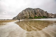 Morro Rock is reflected on the wet sand in Morro Bay, California.