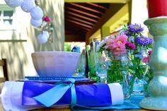 Original y cálido almuerzo en el jardín de la casa. Armado de mesa con flores en frascos de vidrio y combinación de vajilla de distintos estilos y colores.